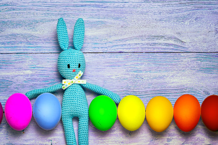 Amigurumi toy easter bunny with colorful eggs in a row on a wooden table - easter background with copy space