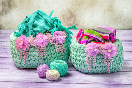 trifles: Handmade cosiness. Two crocheted baskets for feminine trifles, decorated with floral lace. Stock Photo