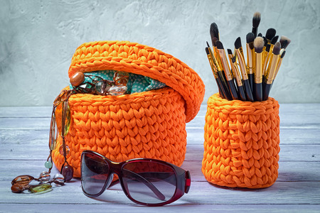 trifles: orange knitted baskets with brushes for make-up and feminine trifles