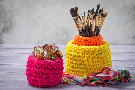 trifles: Colorful knitted baskets with brushes for make-up and feminine trifles