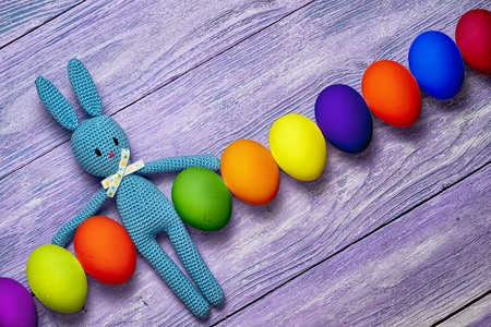 Amigurumi toy easter bunny with diagonal row of colorful eggs on a wooden table - easter background with copy space Stock Photo