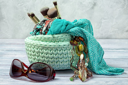 Knitted baskets for trivia with brushes for make-up, scarf and bead with sunglasses. Woman lifestyle concept. Stock Photo