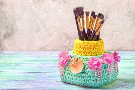 Knitted baskets with brushes for make-up, decorated wit floral lace with fringe and paper tag. Copy space for your lifestyle blog.