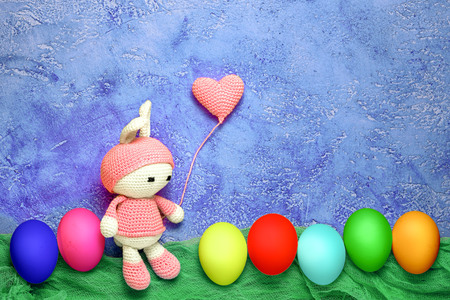 Amigurumi toy easter bunny bunny and crocheted heart shaped balloon with colorful eggs in a row - easter greeting card with copy space Stock Photo