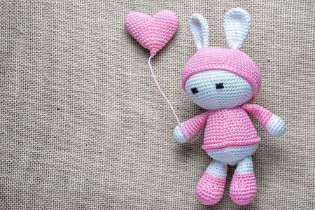 Crochet childrens soft toy bunny wielding knitted balloon on the sackcloth background, with copy space.