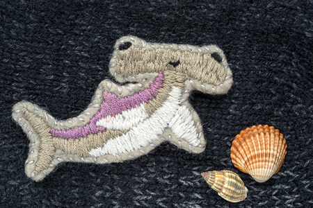 pez martillo: hand embroidered brooch in the form of a hammer fish and sea shells on a crafts knitting background