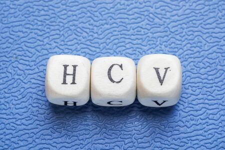 hsv: Word hsv (hepatitis c virus) on a wooden cubes on a blue background Stock Photo