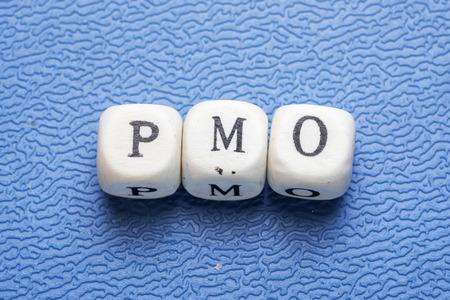 Fassen Sie pmo (Projektmanagementoffizier) auf hölzerne Würfel auf einem blauen Hintergrund ab