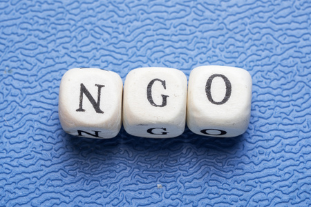 Word NGO (non-governmental organization) on a wooden cubes on a blue background 免版税图像