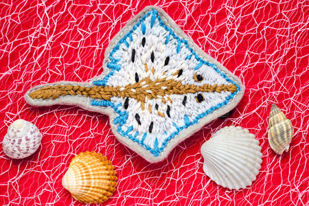 embroidered: hand embroidered ramp on a red background among seashells Stock Photo