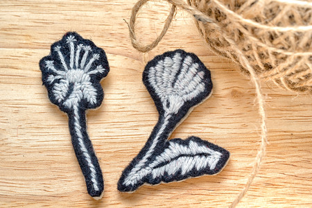Two home-made embroidered black and white flower on a wooden background with a ball of coarse thread