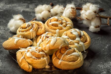 danish: fresh delicious cinnamon rolls on the plate on a dark black cement background with cotton boxes behind Stock Photo