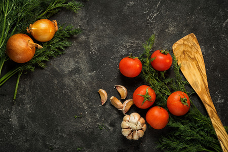 Food background. Raw vegetables on a dark black stone background, top view. Copy space for your text.