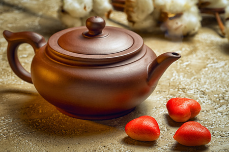 Brown ceramic kettle with three red marzipan in the shape of hearts. Still life on Valentines Day.