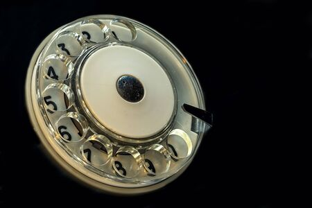 angle view: antique retro telephone circle with numbers, on the black background, angle view with copy space