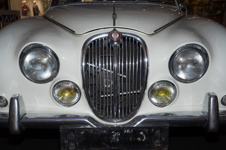 grille: Moscow, Russia - April 02, 2017: Front headlights and grille of a restored white Jaguar S-type, 3,8 litre, Great Britain 1965, close up frontal. Retro car exibition in shopping mall Metropolis. Editorial