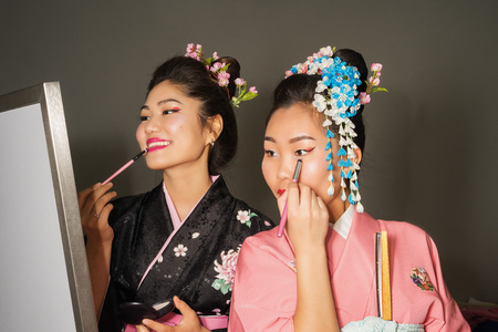asian art: two geisha in traditional japanese kimono make up backstage Stock Photo