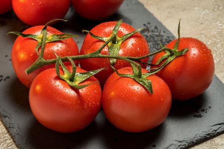 cluster of red ripe wet tomatoes on the table