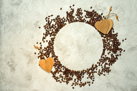 Circle silhouette made from coffee beans with wooden heart tags and copy space, top view. Might be used as pie chart about coffee consumption.