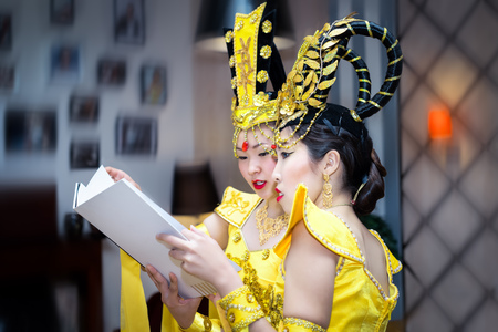 two asian actress in a yellow traditional chinese stage costume reading booklet Stock Photo