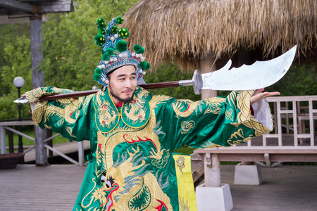 the defender: chinese man in traditional costume with sword outdoor