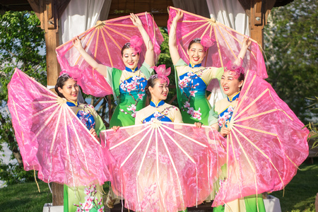 group of five asian women actresses in traditional chinese costumes with fans outdoor