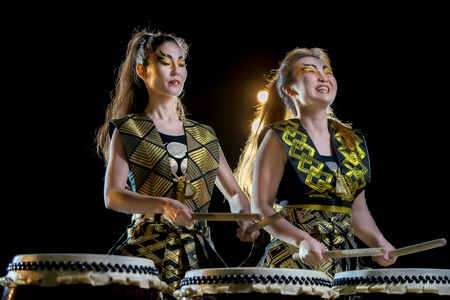 music background: two beautiful asian drummer girl with drumsticks, studio concert shot on a dark background. Stock Photo