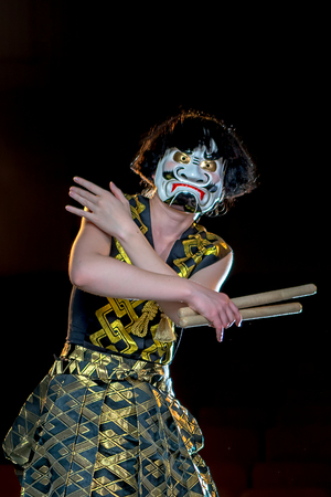 1 person: drummer girl in white demon mask stands with her hands cross holds the drumsticks, studio shot on a dark background.
