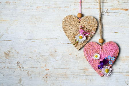 two hearts with small flowers hanging on a wooden background with copy space