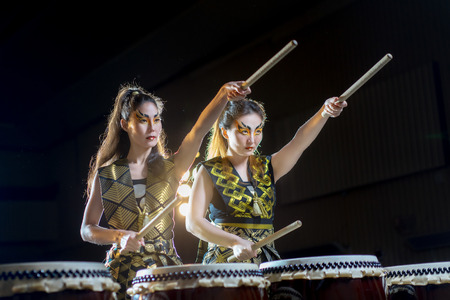 soltería: two beautiful asian drummer girl with drumsticks, studio concert shot on a dark background. business concept of purposefulness and goal setting