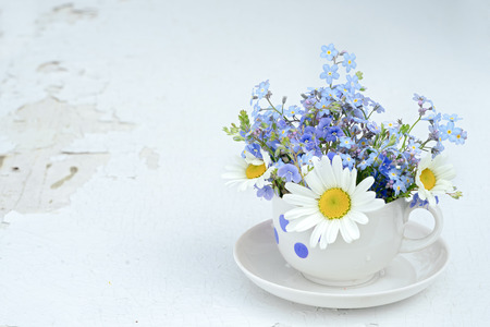 bouquet of forget me not and chamomiles wild flowers in tea cup on a white wooden table with copy space. concept of holiday background.