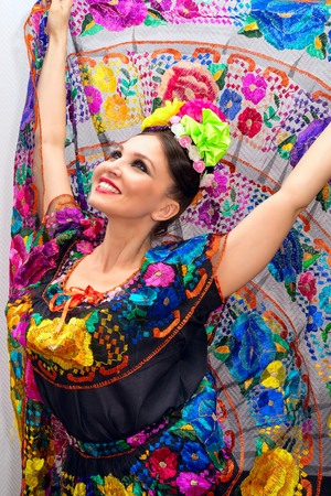 Beautiful smile mexican woman in traditional mexican dress hands up holding the skirt as background as peacock