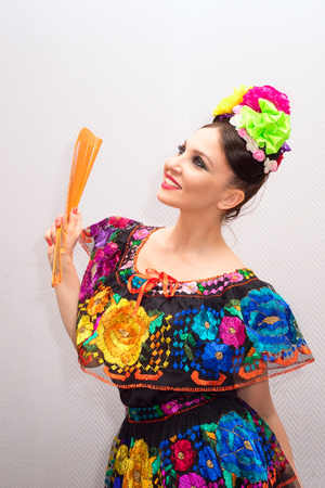 fancywork: Beautiful smile mexican woman in traditional mexican dress with fan