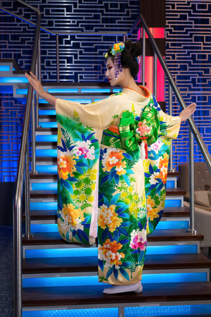 Geisha in traditional chinese floral kimono with bow, standing on a staircase Stock Photo