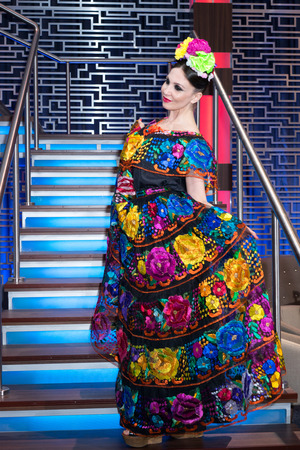 Mexican woman in an embroidery traditional dress standing on the staircase Stock Photo