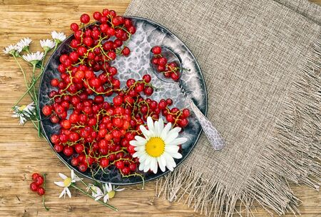 Red currants in a forged metal plate on a wooden table, top view with copy space