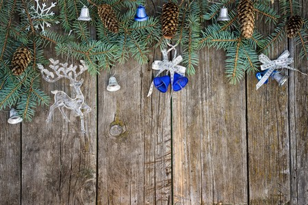 table top: christmas frame from fir tree branches, cones, bells and reindeer toy on a wooden table. top view with copy space for your text.