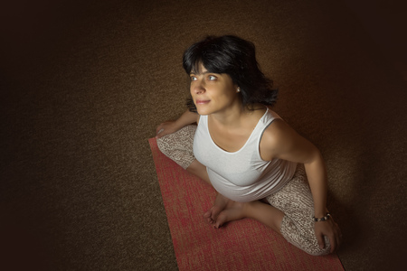 40 week pregnant middle aged caucasian woman sitting in asana doing yoga exercise. Top view, dark colored. Copy space for your text.