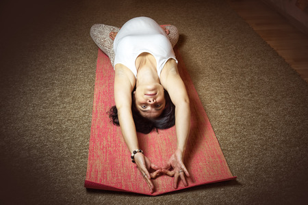 40 week pregnant middle aged caucasian woman sitting in asana doing yoga exercise. Top view, dark colored. Thunderbolt Pose.