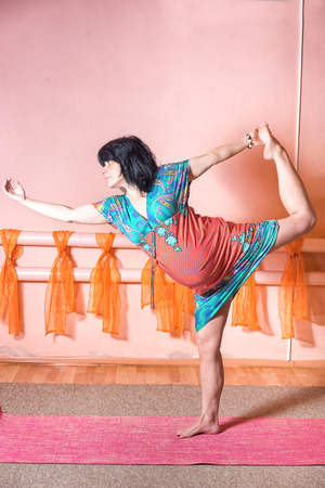 bow belly: Healthy lifestyle maternity concept. 40 week pregnant middle aged caucasian woman wearing dress standing on the one leg in asana doing yoga exercises.