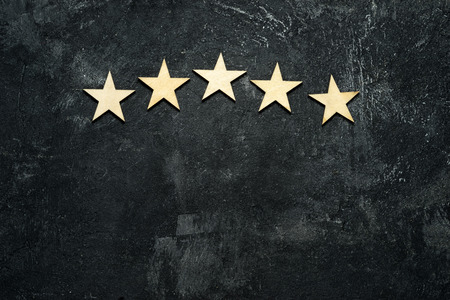 Five wooden stars located in the form of an arch or arc in the upper part of a dark cement background. Conceptual of service rating and quality of trade. Top view, copy space for your text.