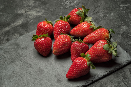 strawberry on a black stone tray laying on a black rustic cement background, side angle view with copy space for your text.
