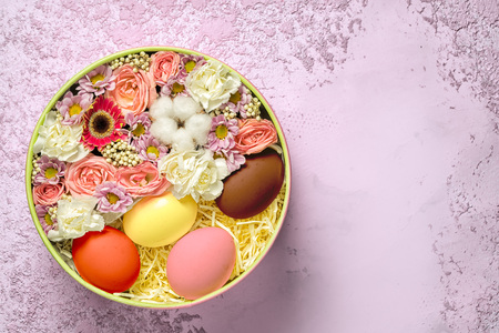 easter eggs with flowers in a circle plate on a pink textured cement background, top view with copy space