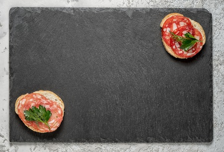 two sandwiches with smoked sausage on an opposite corners of a black stone cheese board, top view with copy space Stock Photo