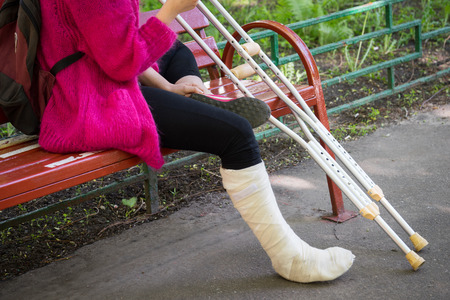 unrecognizable girl sits on the street on a bench with a broken leg and crutches