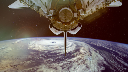 Typhoon and spacecraft above the Earth. Satellite view. Stock Photo