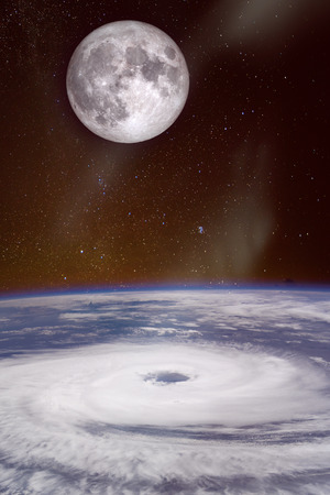 View from space of a giant hurricane over the ocean with full moon in background.