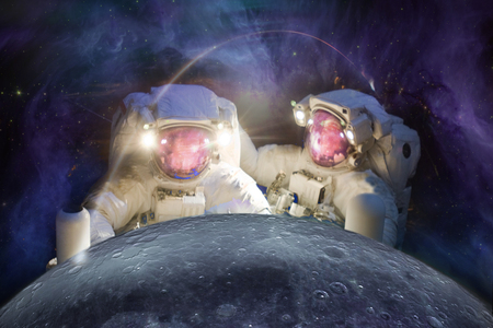 Two huge astronauts observe the Moon against the  of the galaxy. Stock Photo