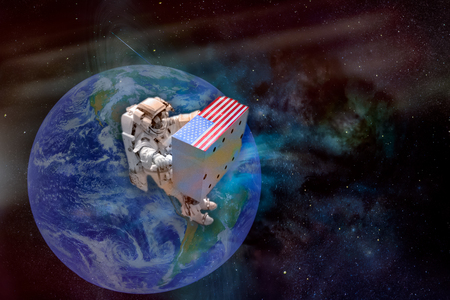 Astronaut in outer space holding a huge box with USA flag on a planet Earth background. Delivery worldwide concept. Copy space on the box. The elements of this image furnished by NASA.