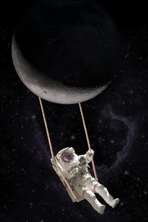 Astronaut swings on a rope swing attached to the moon, in the open space. Фото со стока